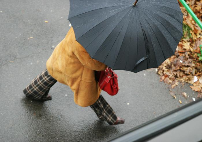 Een vrouw met paraplu als metafoor voor klachten over TVN Zorgt