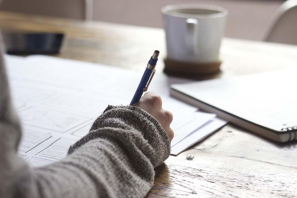 schrijvende hand met documenten over cliëntervaringen