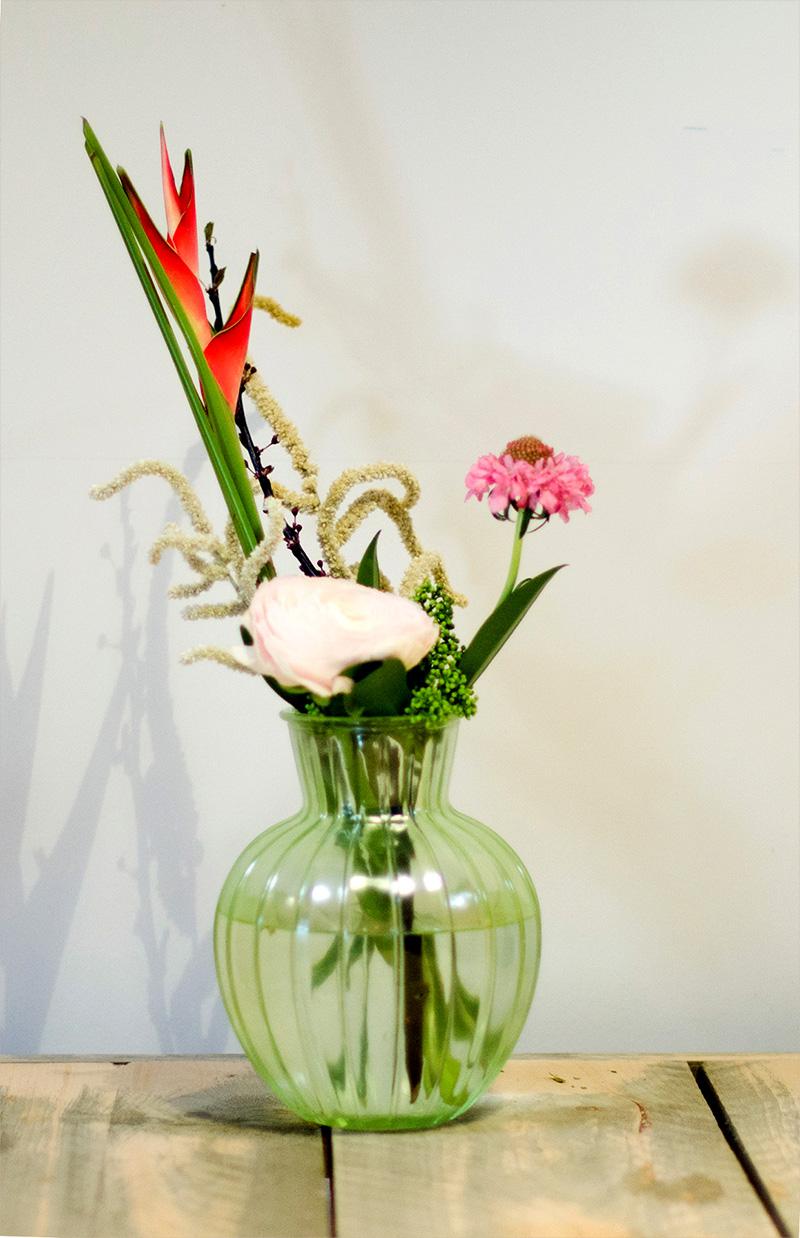 kleurrijke bos bloemen in groene vaas op tafel bij TVN Zorgt