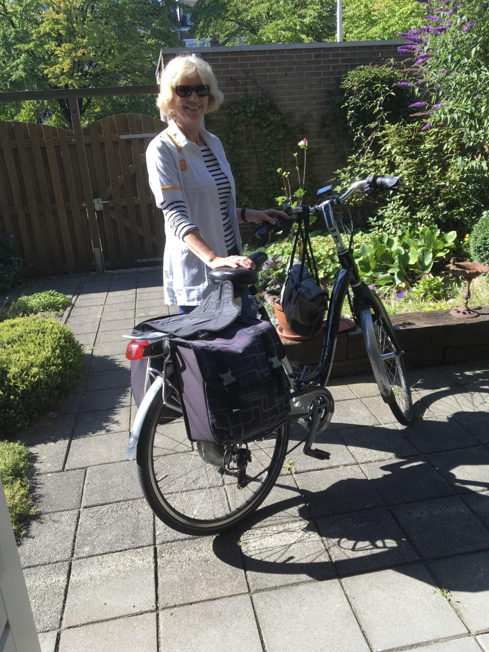 Henny vertrouwenspersoon TVN Zorgt Nijmegen op de fiets in de tuin