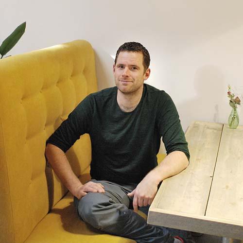 Thomas medewerker TVN Zorgt op Kantoor met gele bank